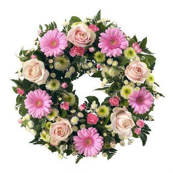 Rosa blommor i en begravningskrans